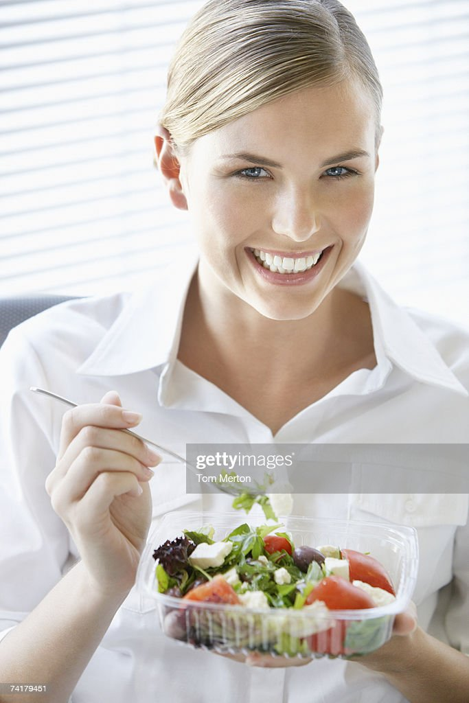 Businesswoman at desk eating salad : Stock Photo