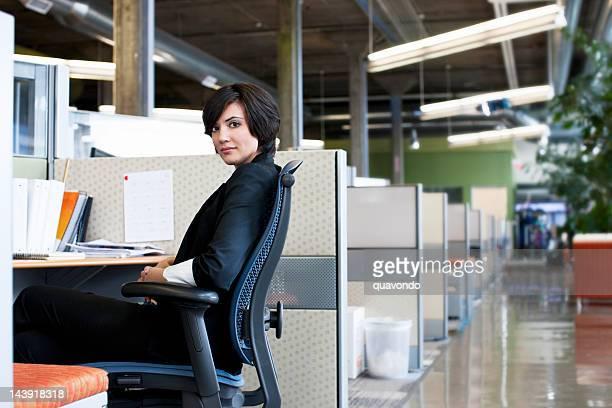 Geschäftsfrau an Schreibtisch in Trennwand Büro, Lächeln über der Schulter