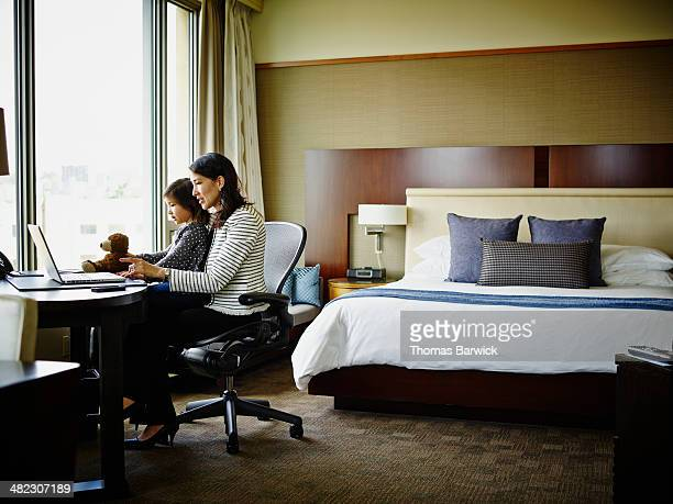 Businesswoman at desk in hotel room with daughter