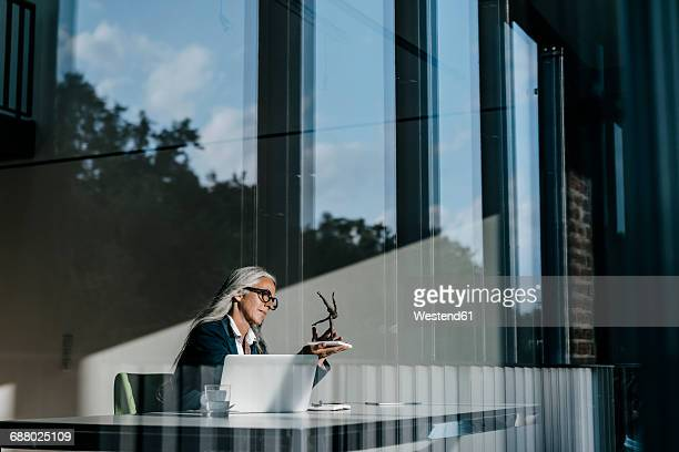 Businesswoman at desk looking at sculpture