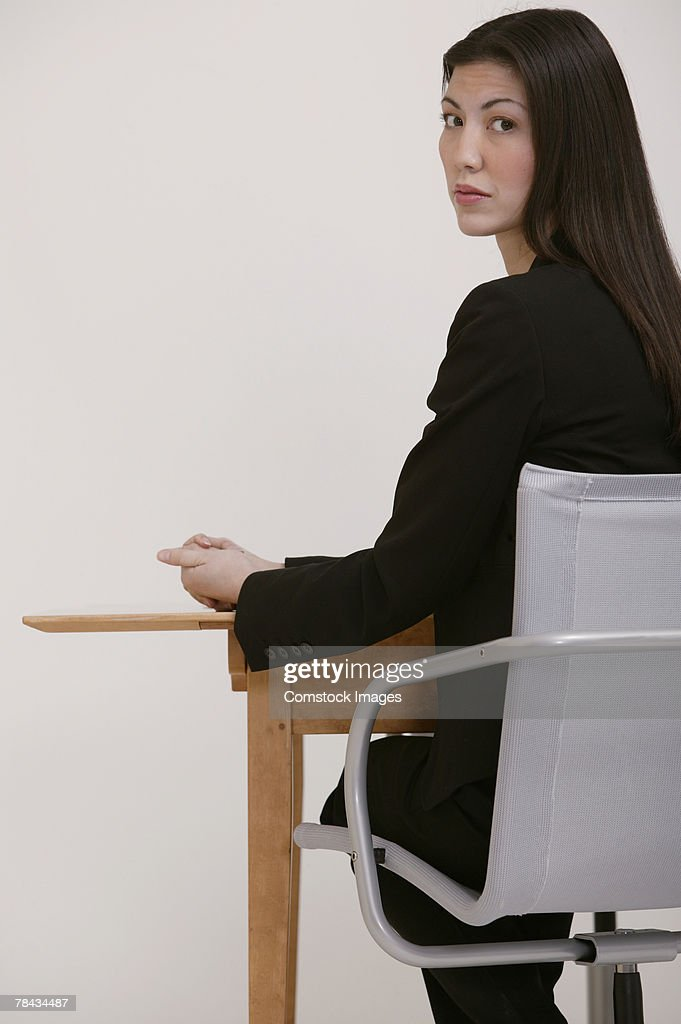 Businesswoman at desk looking over her shoulder : Stockfoto
