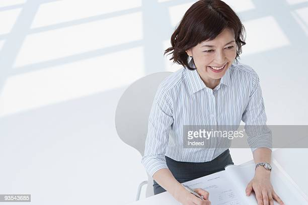 Businesswoman at desk, smiling