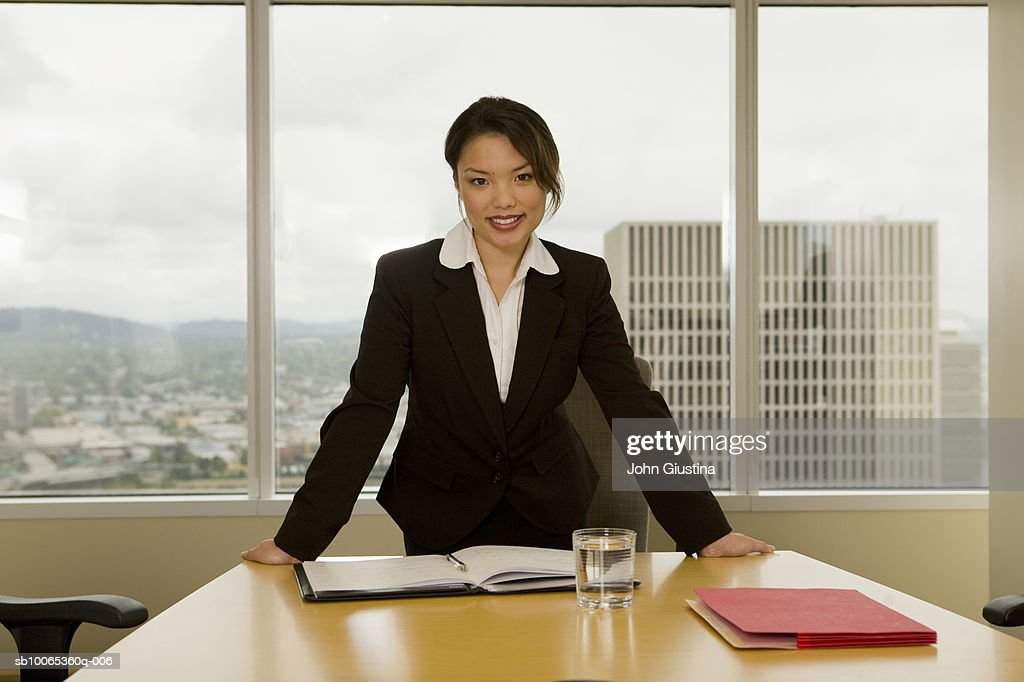 Businesswoman at desk, smiling, portrait : Foto stock