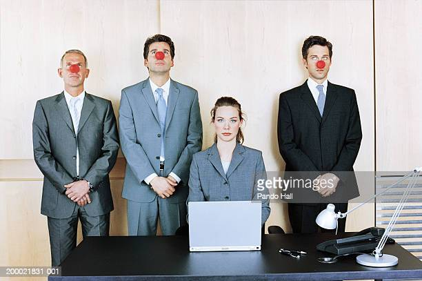 businesswoman at desk, three colleagues behind wearing clown noses - clown's nose stock photos and pictures