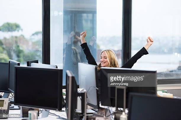 Businesswoman at desk with arms out, cheering