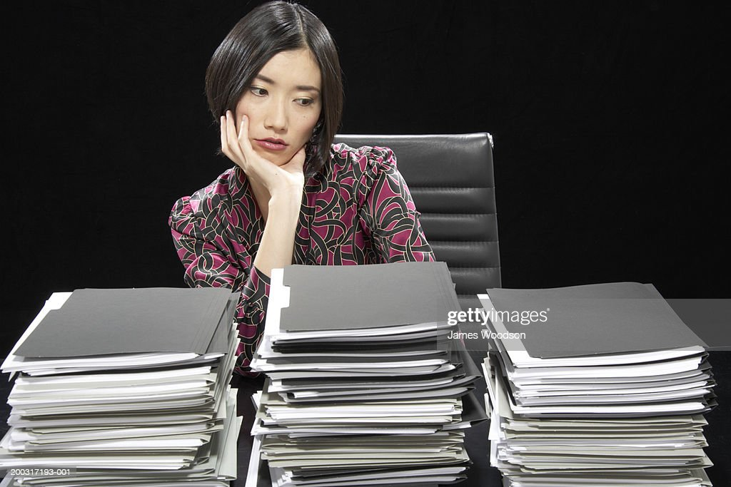 Businesswoman at desk with stacks of documents, resting chin on hand : Stock Photo