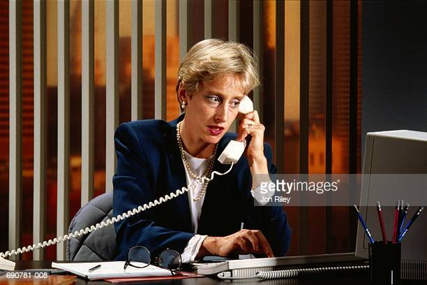 Businesswoman at desk,on telephone, looking at computer screen