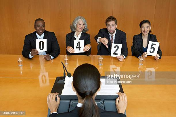 Businesswoman at interview, executives holding score cards, jeering