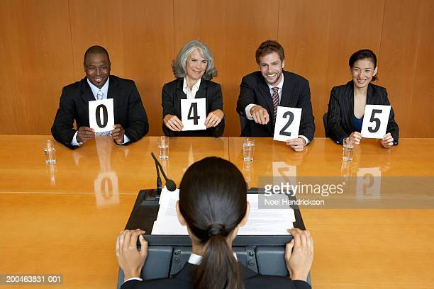 Businesswoman at interview, executives holding score cards, smiling