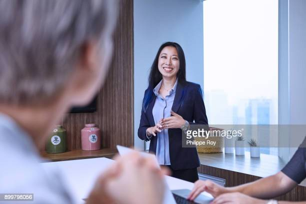 Businesswoman at meeting in boardroom, looking at colleague smiling