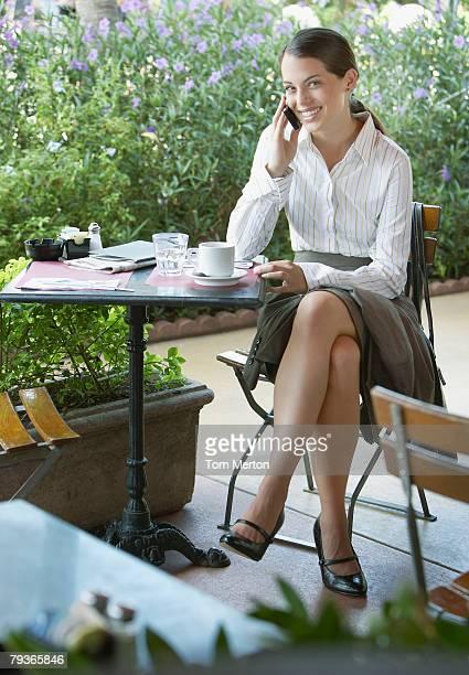 donna in carriera al patio esterno tabella sul cellulare - gambe accavallate foto e immagini stock