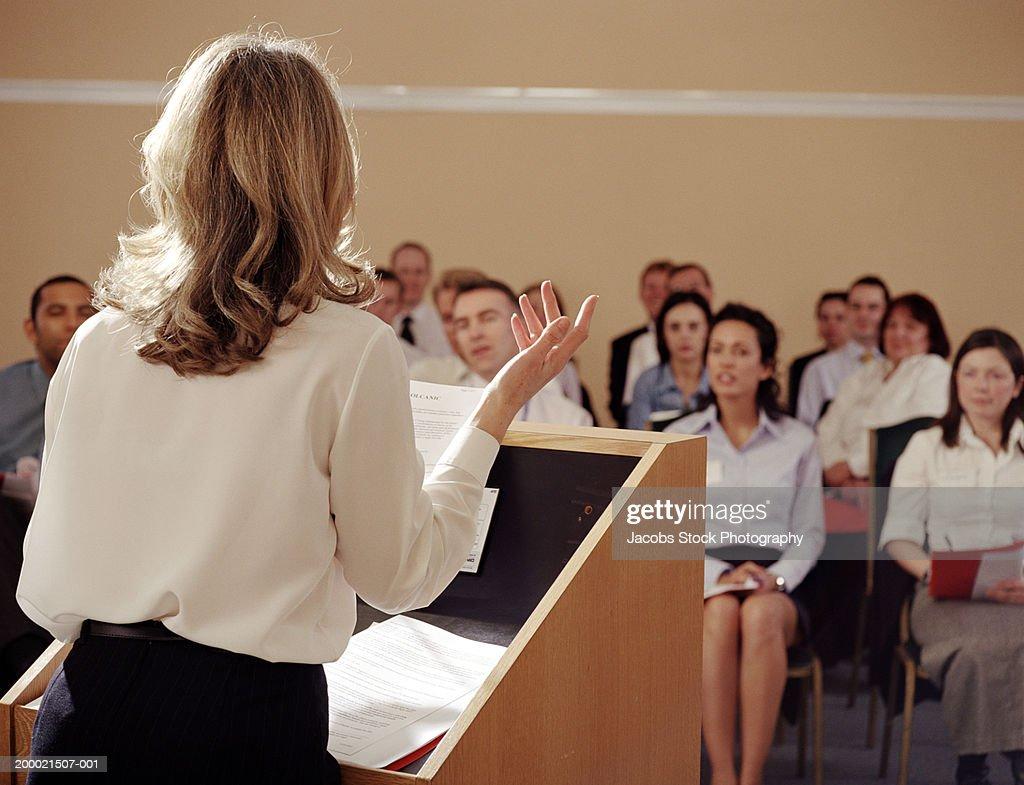 Businesswoman at podium addressing colleagues, rear view : Foto de stock