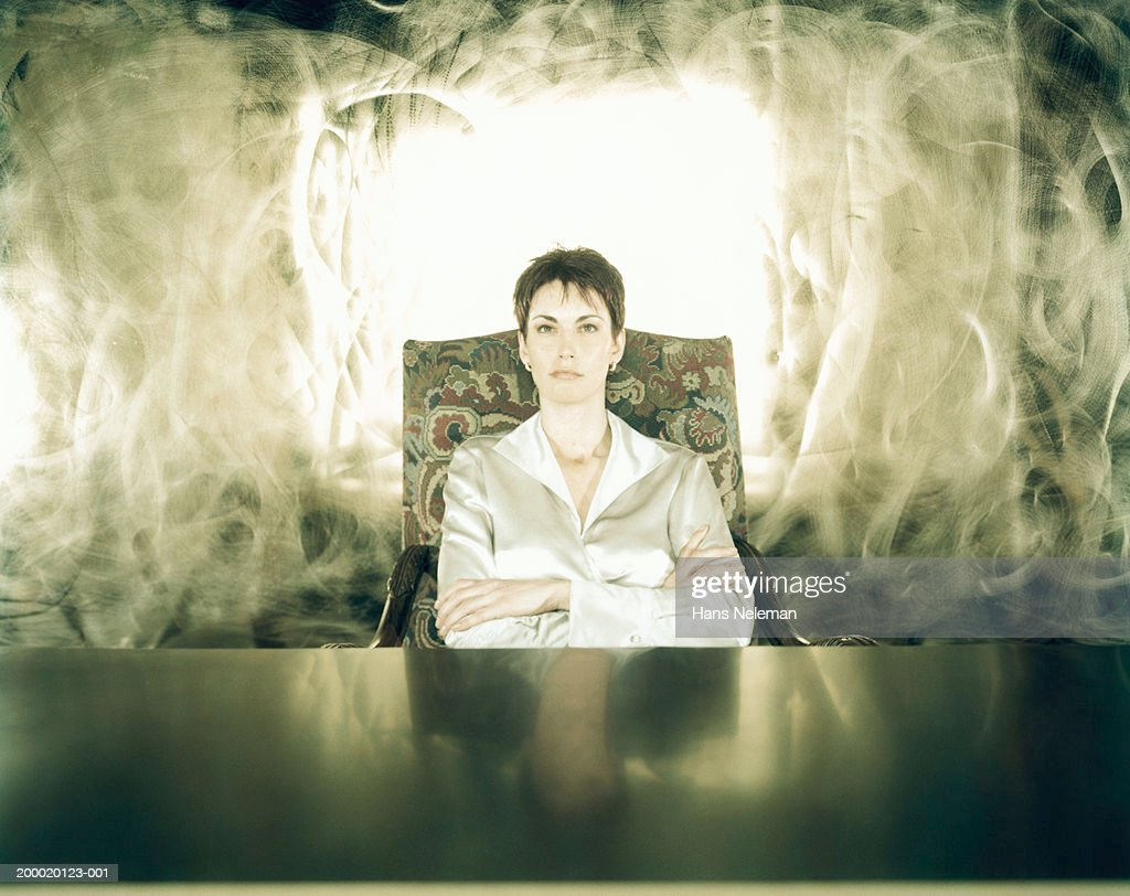 Businesswoman at table, with arms folded (digital composite) : Stock Photo