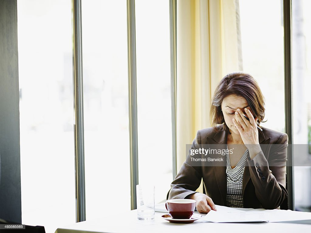 Businesswoman at table with head resting on hand : Stock Photo