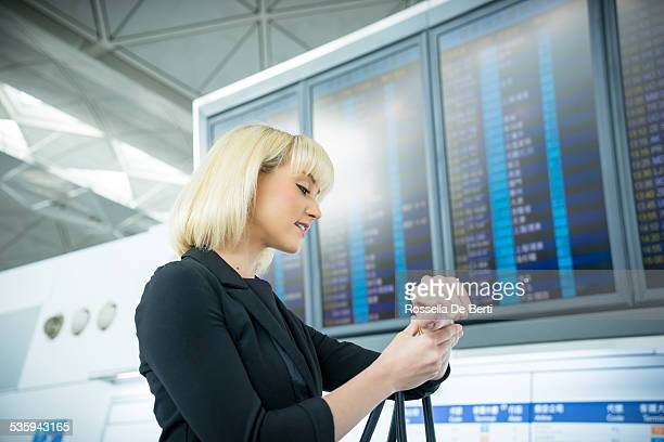 Businesswoman At The Airport Checking Flight Information