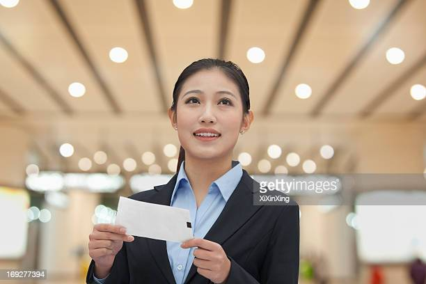 Businesswoman at the airport with airplane ticket