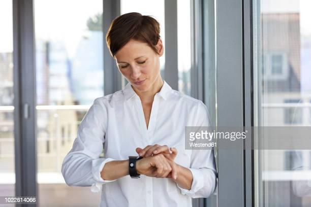 businesswoman at the window in office checking the time - blick nach unten stock-fotos und bilder