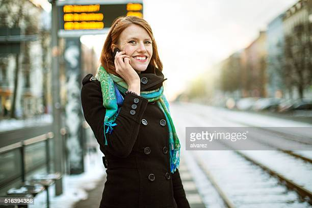 Businesswoman at train station talking on mobile phone