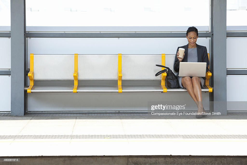 Businesswoman at train station using laptop : Stock Photo