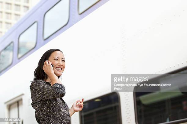 Businesswoman at train station using mobile phone