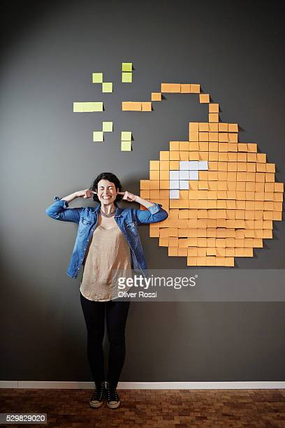 Businesswoman at wall with sticky notes forming a bomb