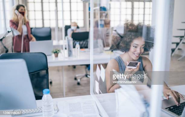 businesswoman at work talking on phone, during covid-19 - business finance and industry stock pictures, royalty-free photos & images