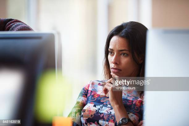 businesswoman at workstation contemplating project - leanincollection stock pictures, royalty-free photos & images