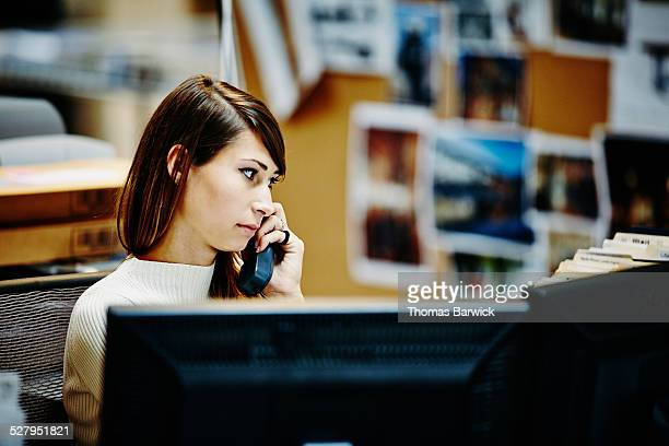 Businesswoman at workstation on phone with client