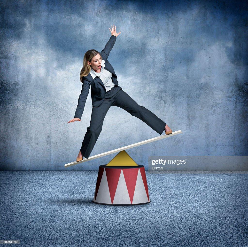Businesswoman Balancing On A Circus Pedestal : Stock Photo