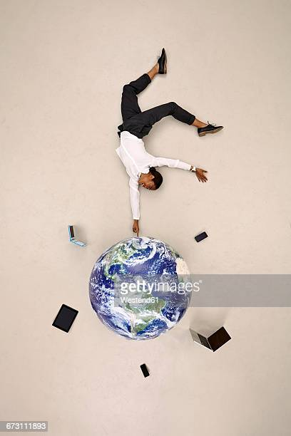 Businesswoman balancing on fingertip on globe with mobile devices
