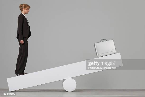 businesswoman balancing on seesaw - gender inequality stock photos and pictures