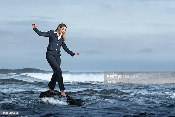 Businesswoman Balancing Precariously On Rock In Ocean