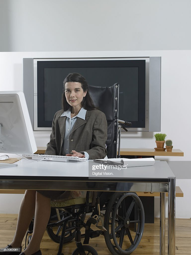 Businesswoman Behind a Table Sitting in a Wheelchair : Stock Photo