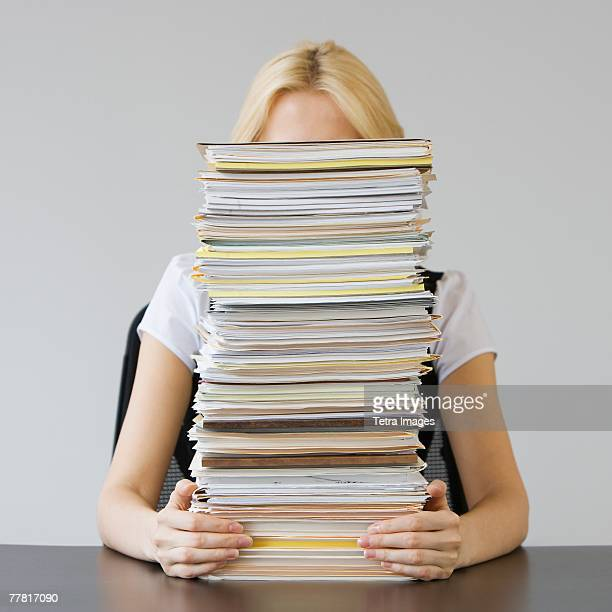 Businesswoman behind stack of paperwork