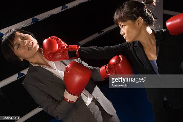 Businesswoman being hit by her opponent in a boxing ring