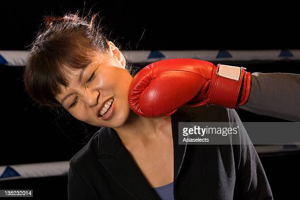 Businesswoman being hit by her opponent