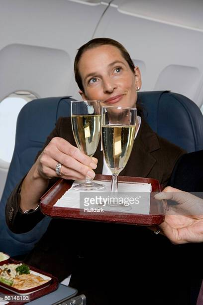 A businesswoman being served champagne on a plane