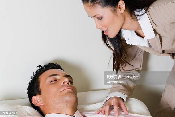 Businesswoman bending over a businessman sitting on a couch