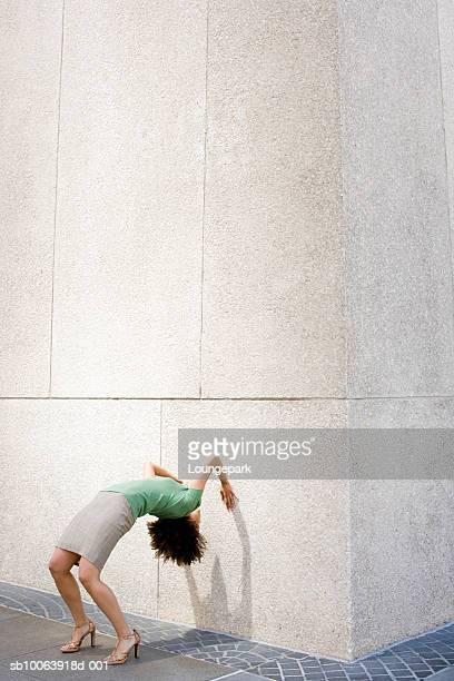 businesswoman bending over backwards against wall - dipping stock photos and pictures