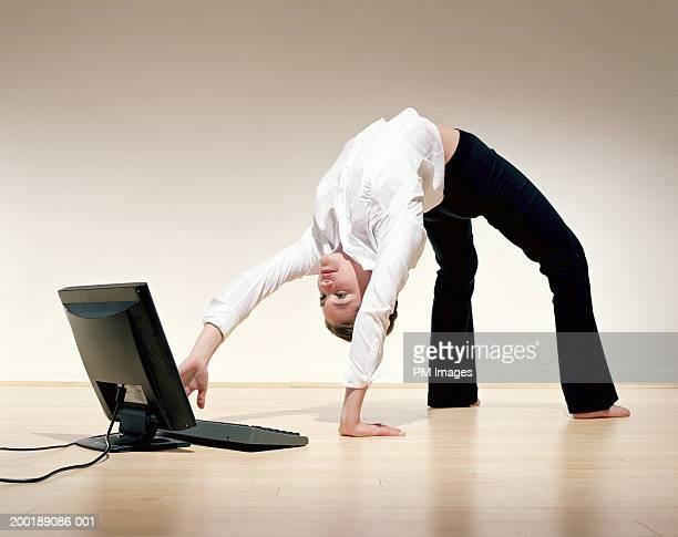 Businesswoman bent over backwards using laptop
