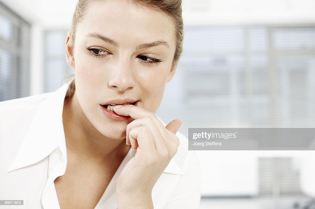 Businesswoman biting fingernails : Stock Photo