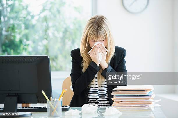 businesswoman blowing nose in office - krankheit stock-fotos und bilder