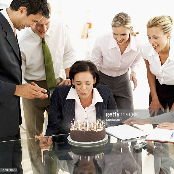 Businesswoman blowing out the candles on her birthday cake
