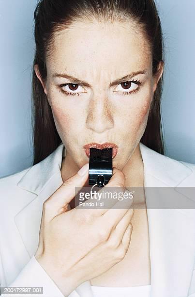 Businesswoman blowing whistle, portrait, close-up