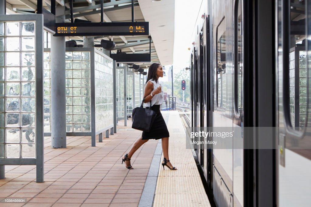 Businesswoman boarding train : Stock Photo