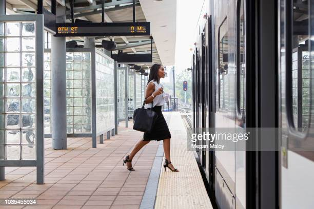 businesswoman boarding train - striding stock pictures, royalty-free photos & images