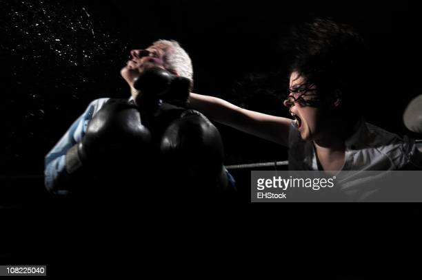 Businesswoman Boxing and Knocking Businessman Out on Black