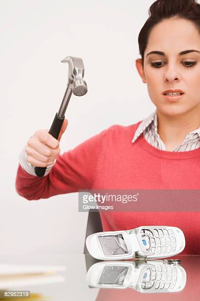 Businesswoman breaking a mobile phone with a hammer