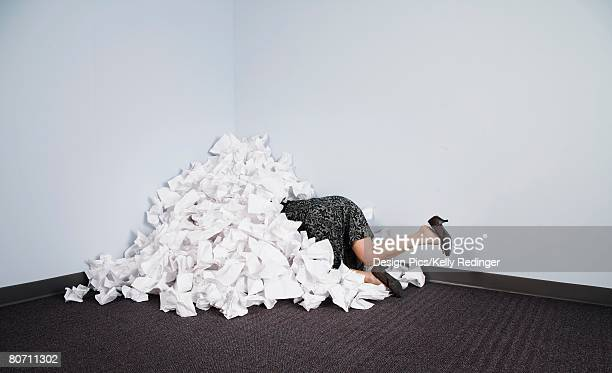 Businesswoman buried in pile of paper