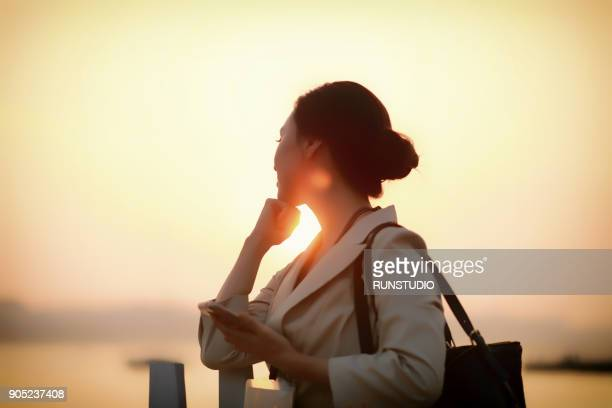 Businesswoman by the riverside with cell phone